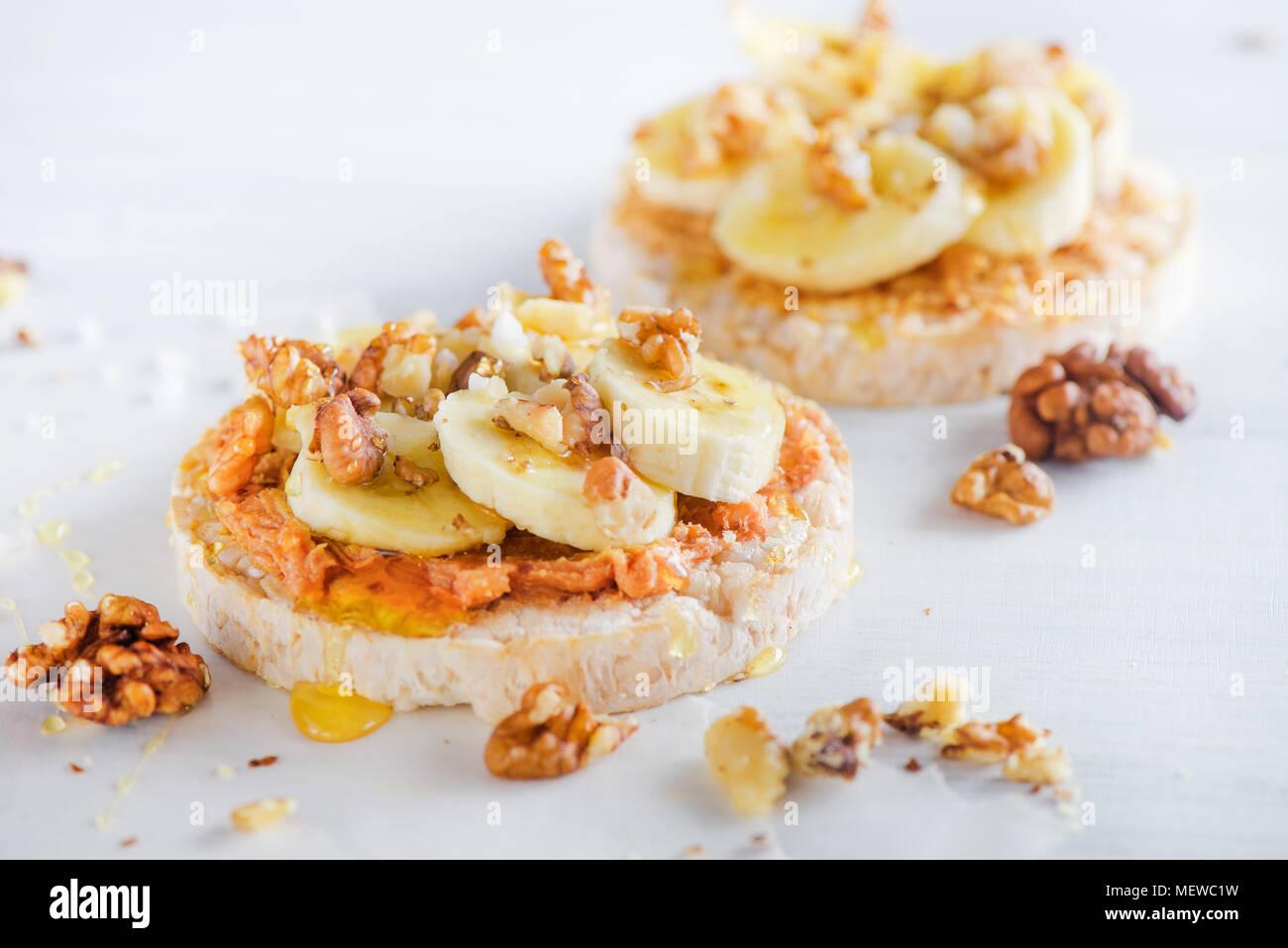 Knäckebrot Banane und Erdnussbutter Snack. Gesundes Frühstück mit Walnüssen und Honig. High key Diät Konzept. Stockbild