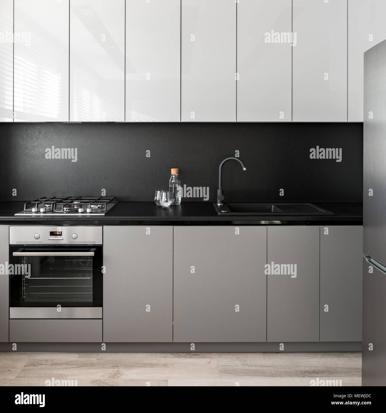 Einfache Küche Einheit In Grau Und Weiß Mit Schwarzen Backsplash Stockbild