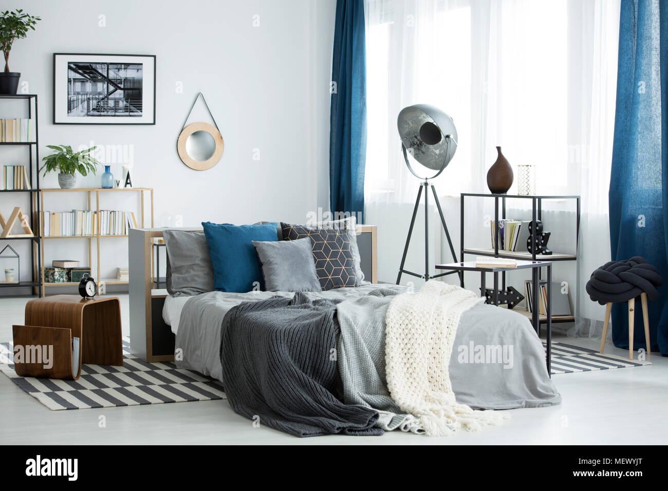 Grau Bettwasche Auf Bett Im Gemutlichen Schlafzimmer Innenraum Mit Lampe Und Pflanzen Auf Regale Mit Buchern Stockfotografie Alamy