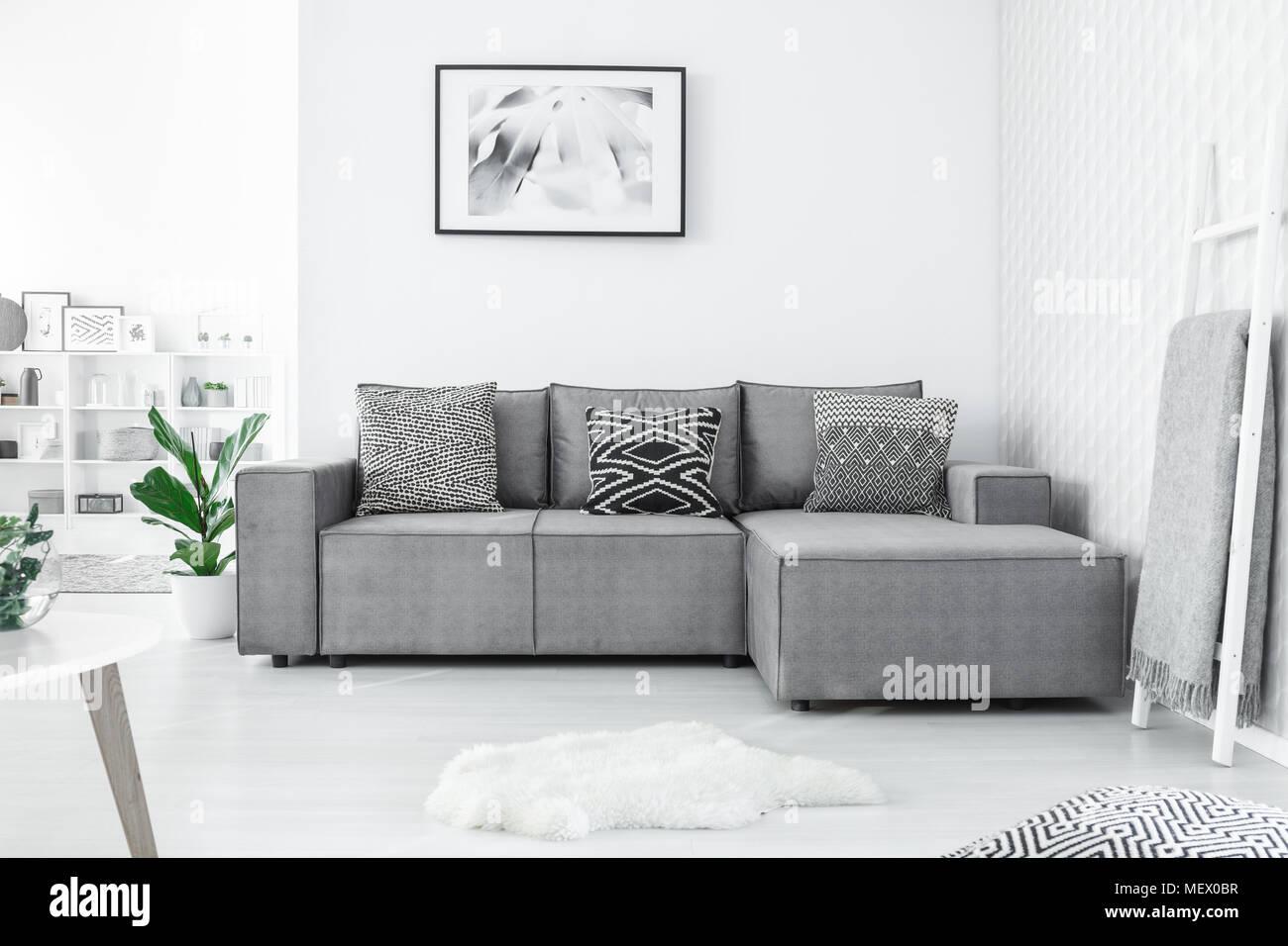 Graue Ecke Couch Mit Drei Gemusterten Kissen Im Hellen Wohnzimmer Interieur  Mit Malerei Und Weissen Teppich Stehend