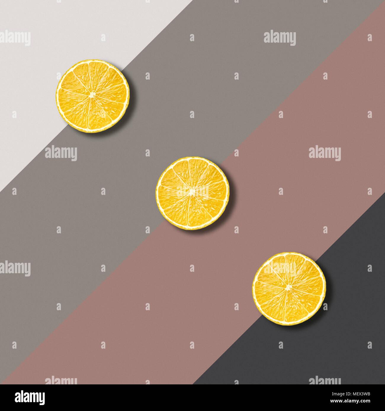Abstraktes Bild mit drei Zitronenscheiben auf farbigen Hintergrund, minimalistische geometrische Essen Fotografie Stockbild