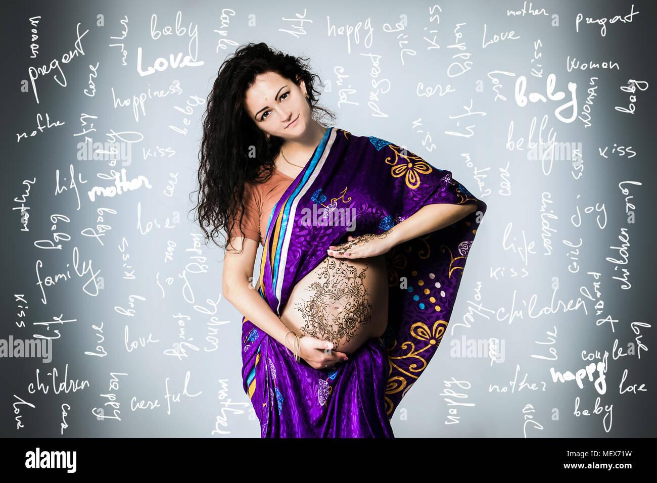 Studio Portrait einer schwangeren Frau in der indischen Sari, einer schwangeren Bauch gemalt mit Henna Stockfoto