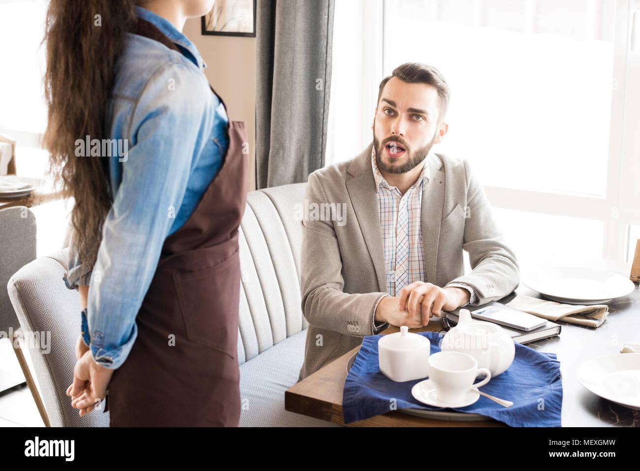 Nachdenklich, Kunde fragt die Kellnerin im Cafe Stockbild