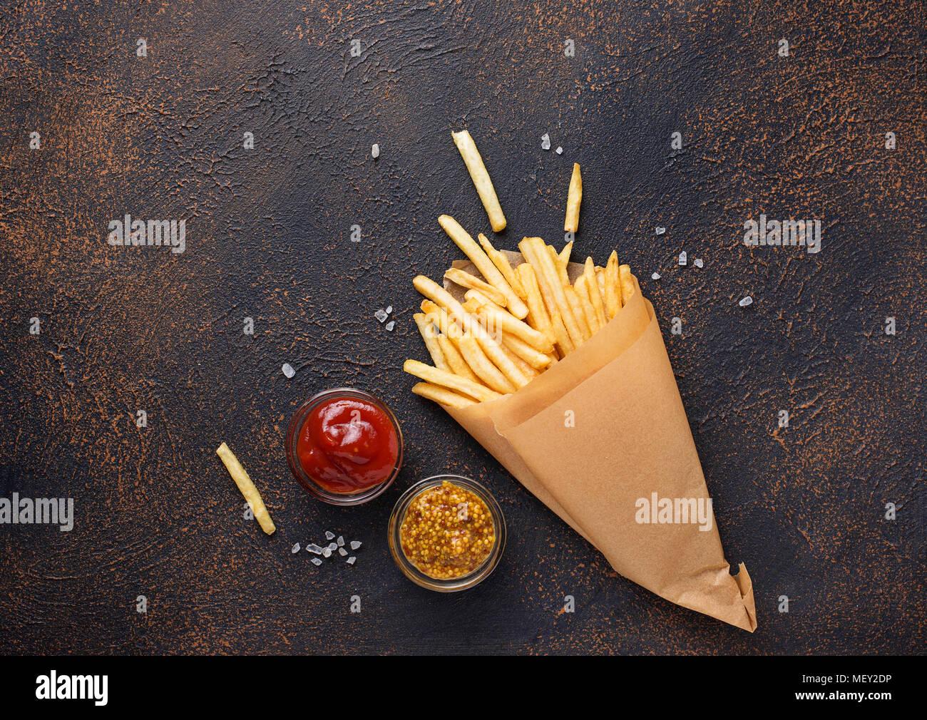 Pommes frites in einer Papiertüte mit Soßen Stockbild