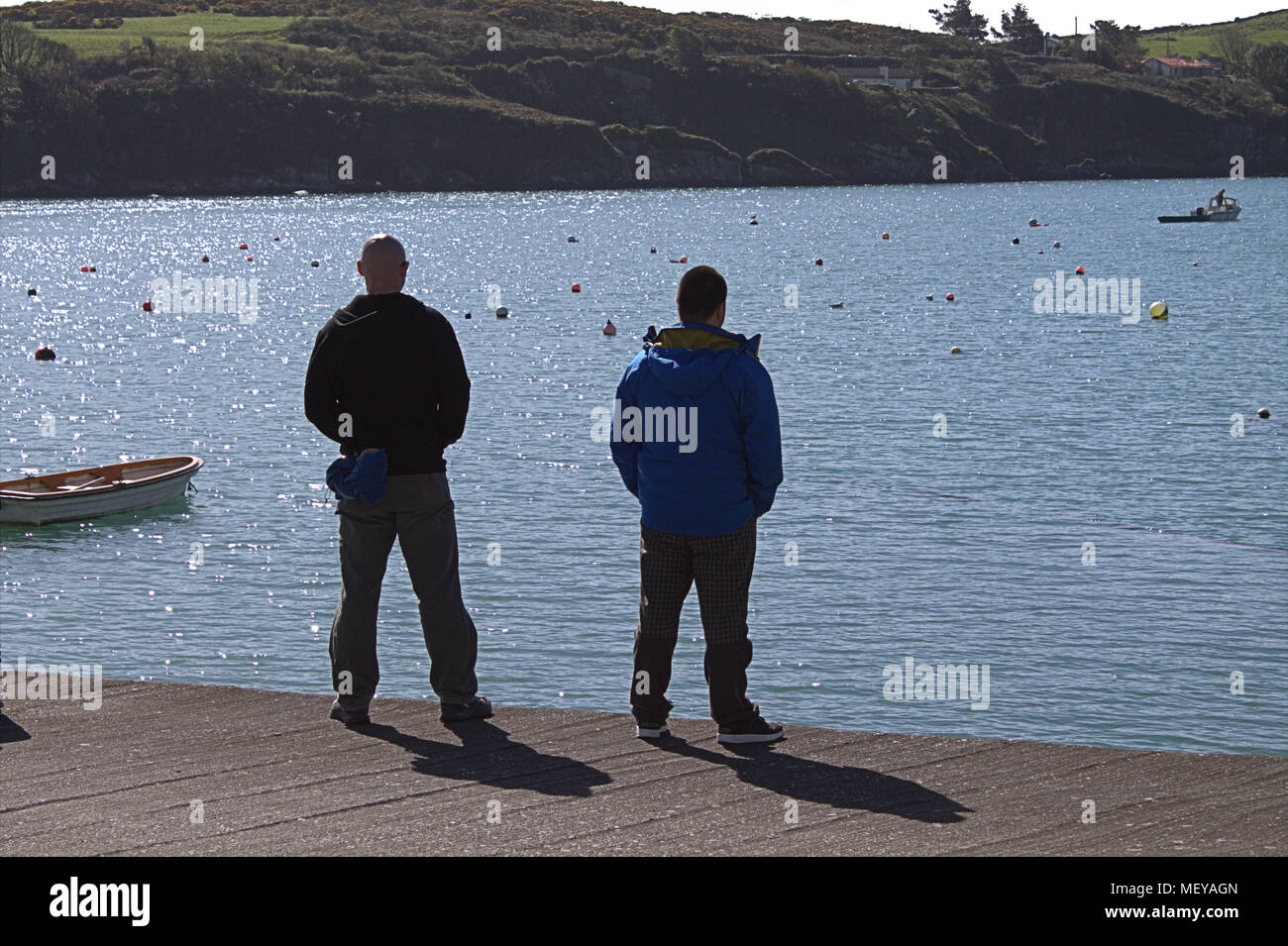 2 im mittleren Alter stehende Männer auf einem Steg im County Cork, Irland beobachten ein Fischerboot in der Ferne. County Cork ein beliebtes Urlaubsziel. Stockbild