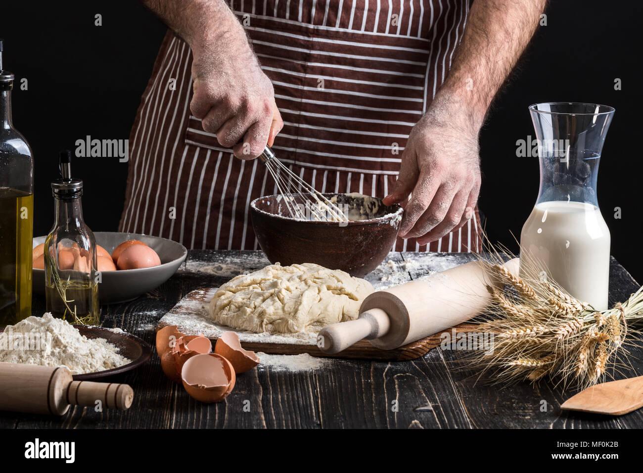 Männliche chef Schlagsahne Eier in die Bäckerei auf hölzernen Tisch. Zutaten für das Kochen von Mehl oder Teig Stockbild