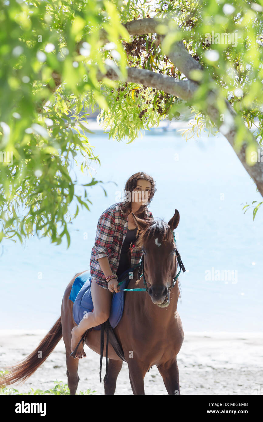 Frau auf pferd am strand