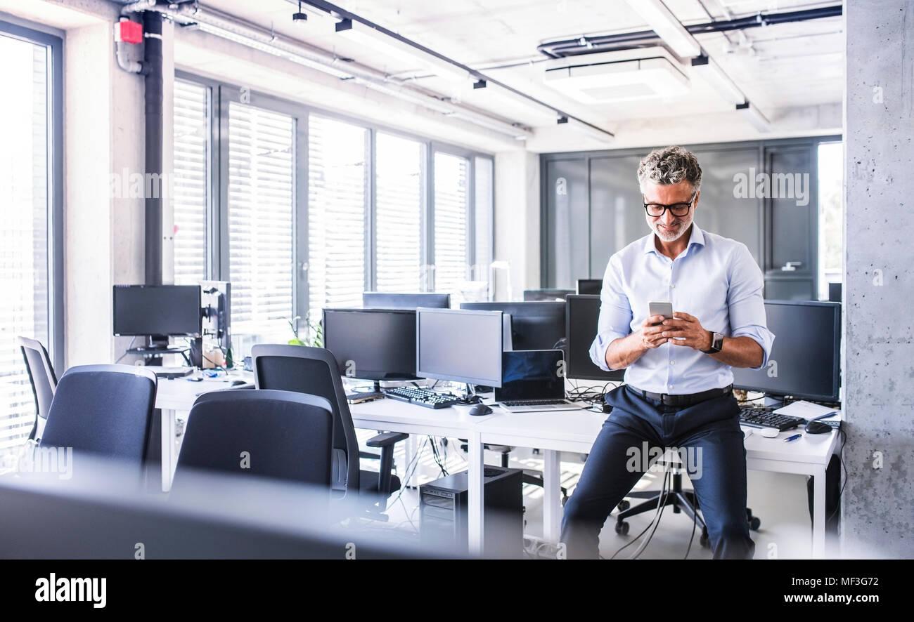 Lächelnd Reife Unternehmer sitzen am Schreibtisch im Büro mit Smartphone Stockbild
