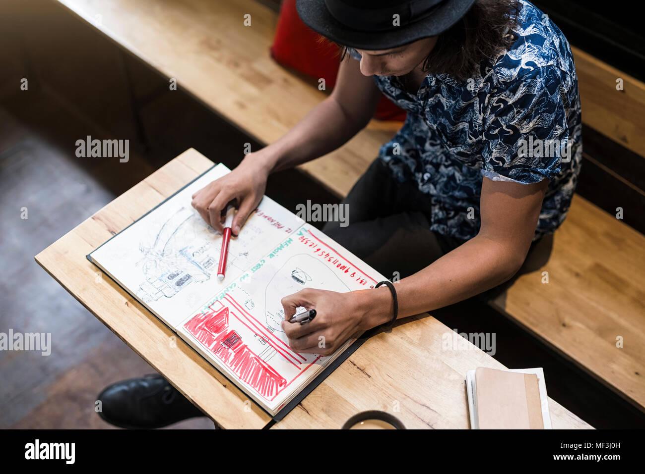 Künstler sitzen im Cafe, Zeichnung in seinem Notebook Stockbild