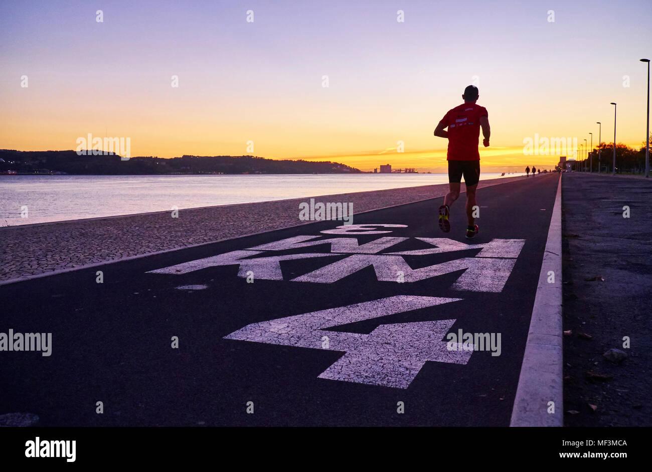 Portugal, Lissabon, den Fluss Tejo bei Sonnenuntergang, Jogger Stockbild