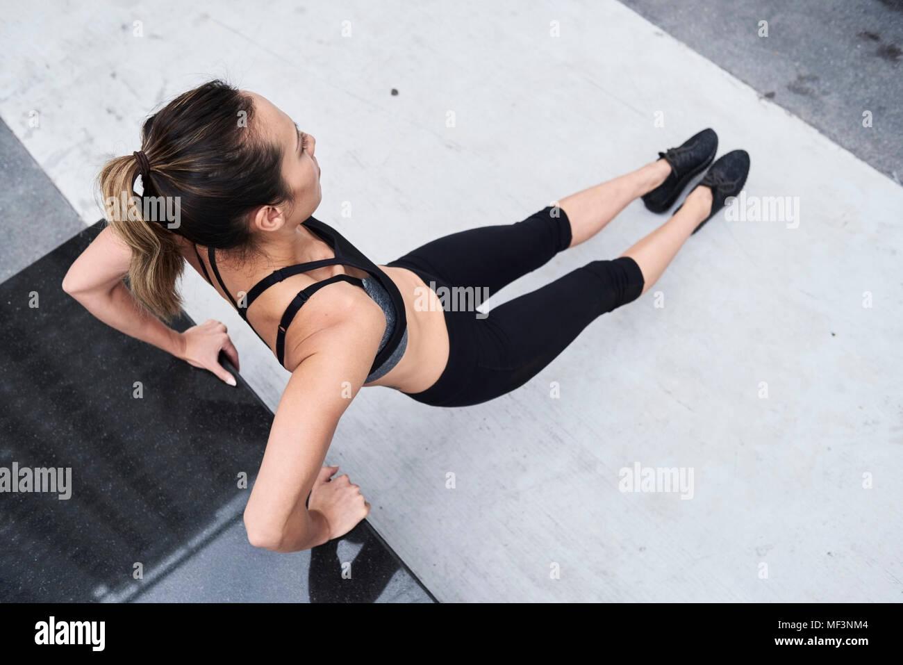 Passende Frau tun Push-ups im Freien Stockbild