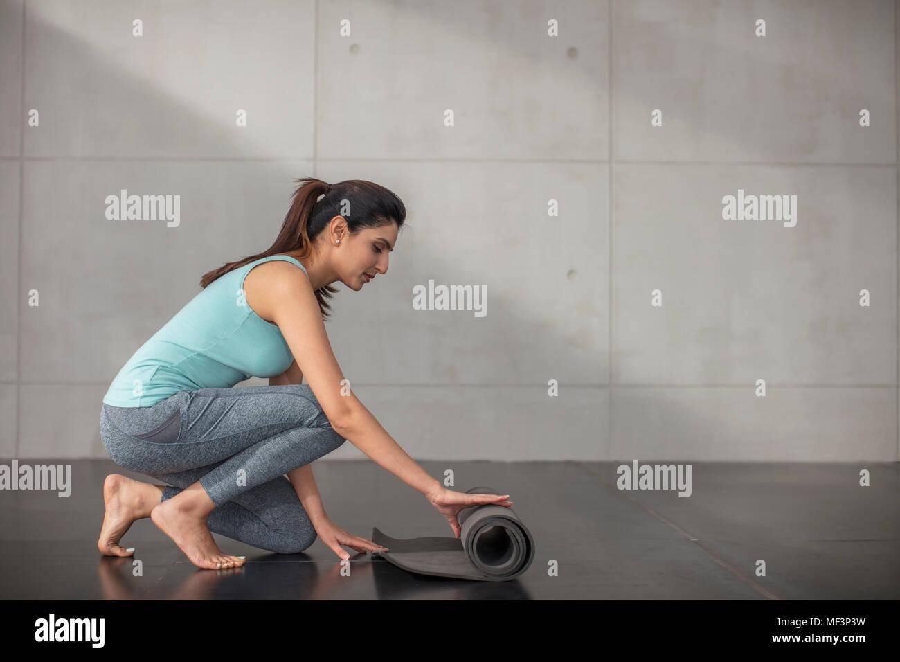 Junge Frau vorbereiten für Yoga Übung im Studio Stockbild