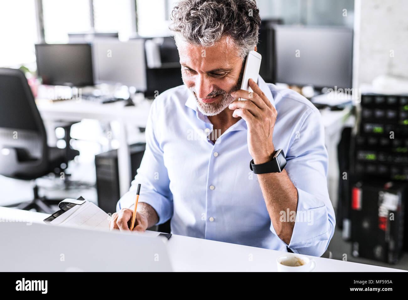 Lächelnd Reife Unternehmer sitzen am Schreibtisch im Büro sprechen auf dem Smartphone Stockbild