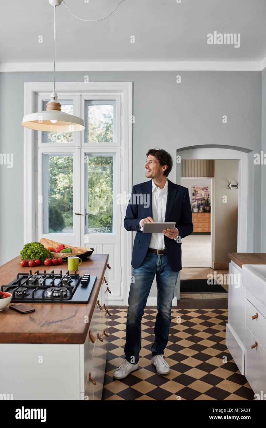 Mann Mit Tablet In Der Küche An Der Decke Lampe Suchen