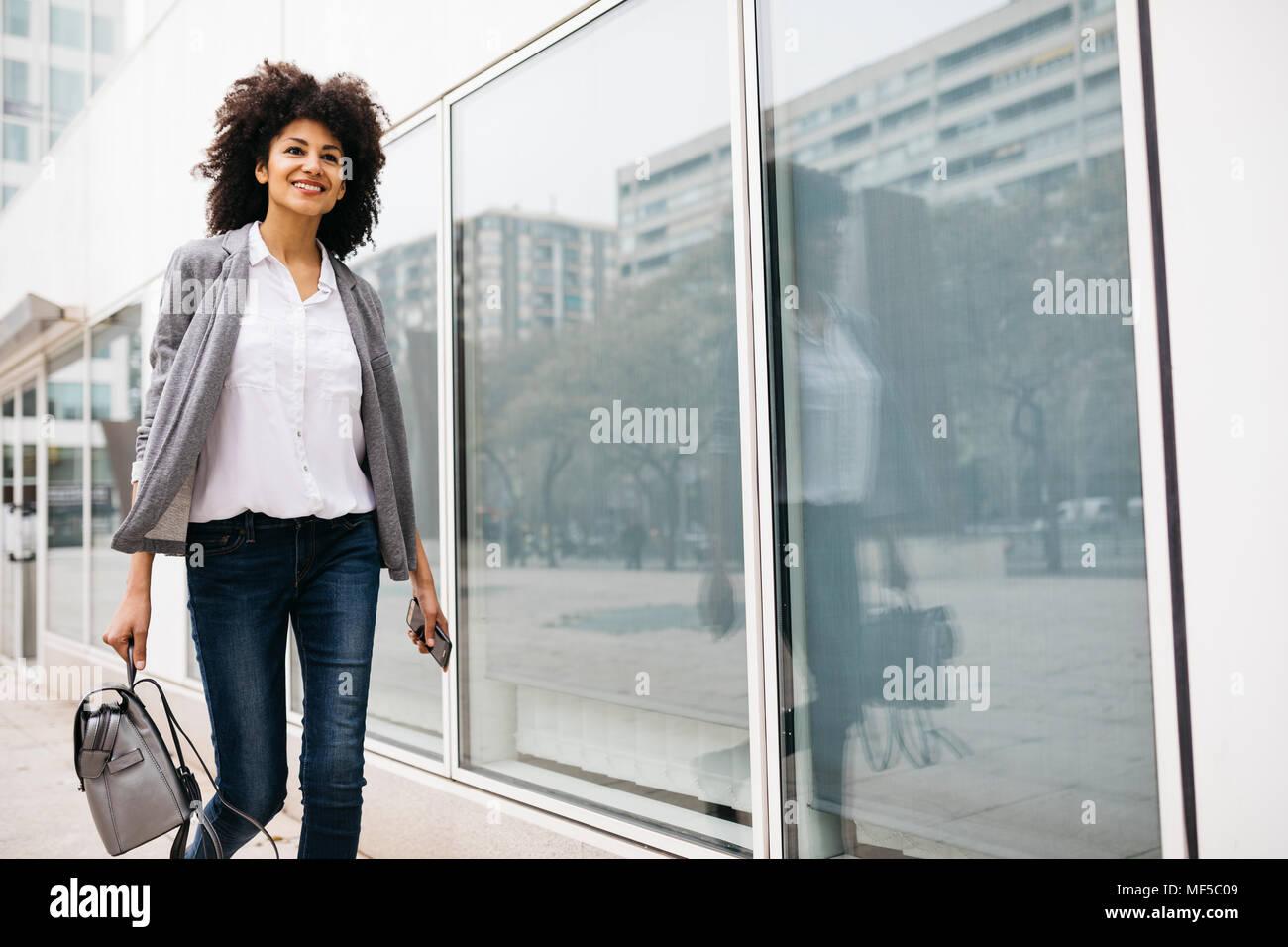 Lächelnde Frau mit Tasche und Smartphone Walking im Freien Stockbild