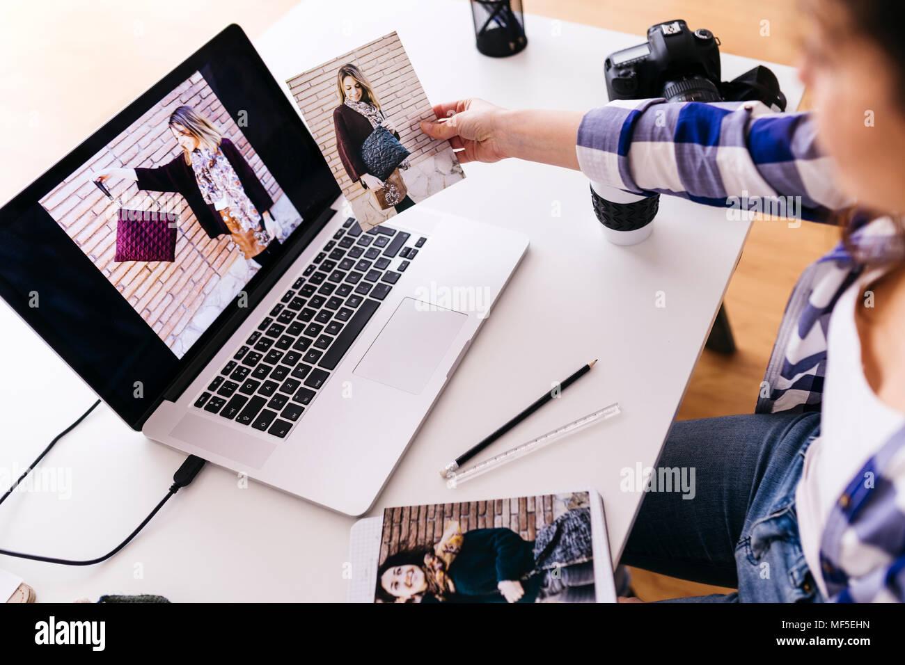 Fashion Designer mit Laptop das Betrachten von Fotos im Studio Stockbild