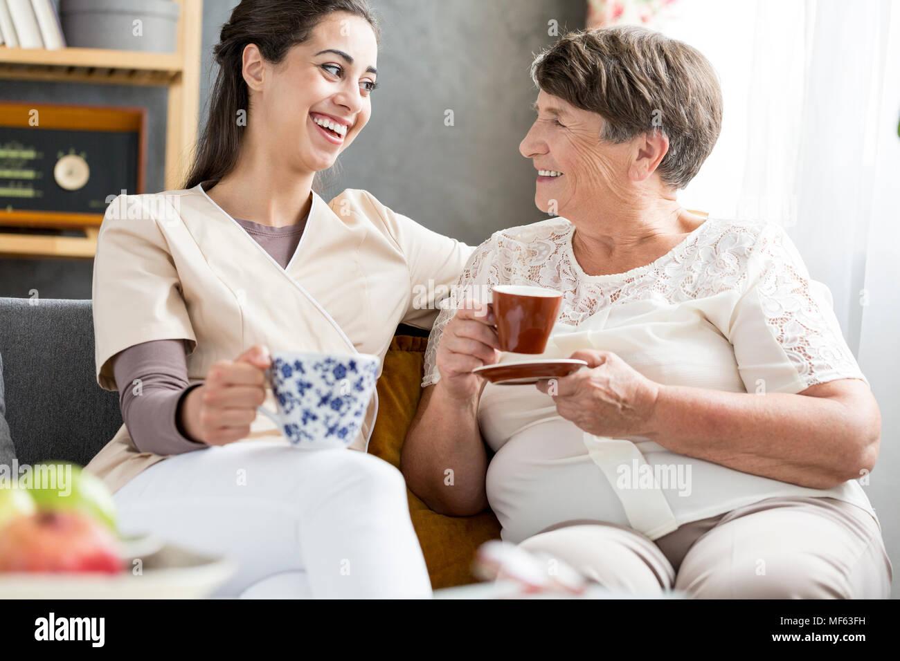 Lächelnd freiwilligen Kaffee trinken mit einem älteren Patienten in ein Pflegeheim Stockbild