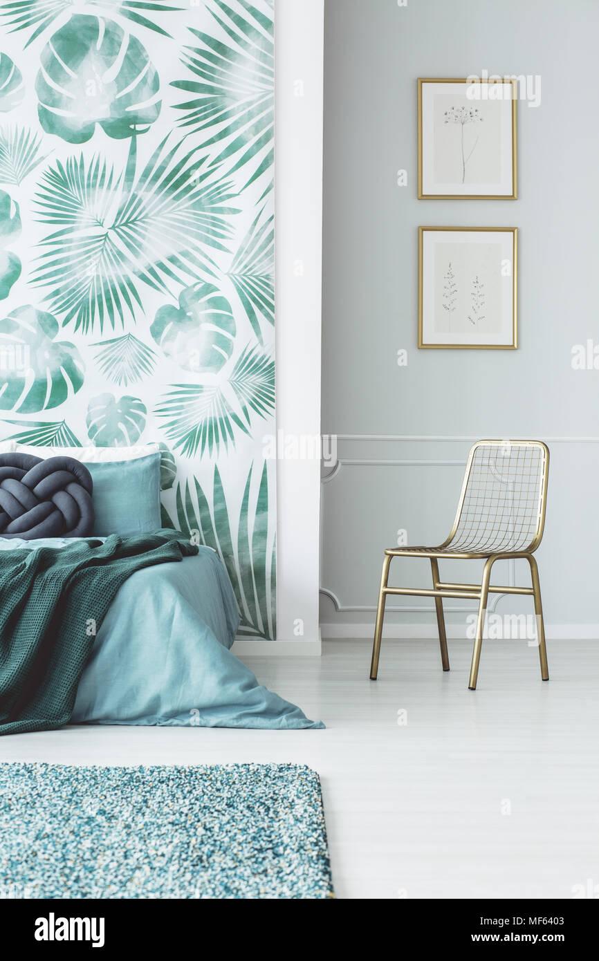 Gold Stuhl Gegen Die Wand Mit Plakaten Im Schlafzimmer Innenraum Mit Blauen Bett Gegen Grune Tapete Stockfotografie Alamy