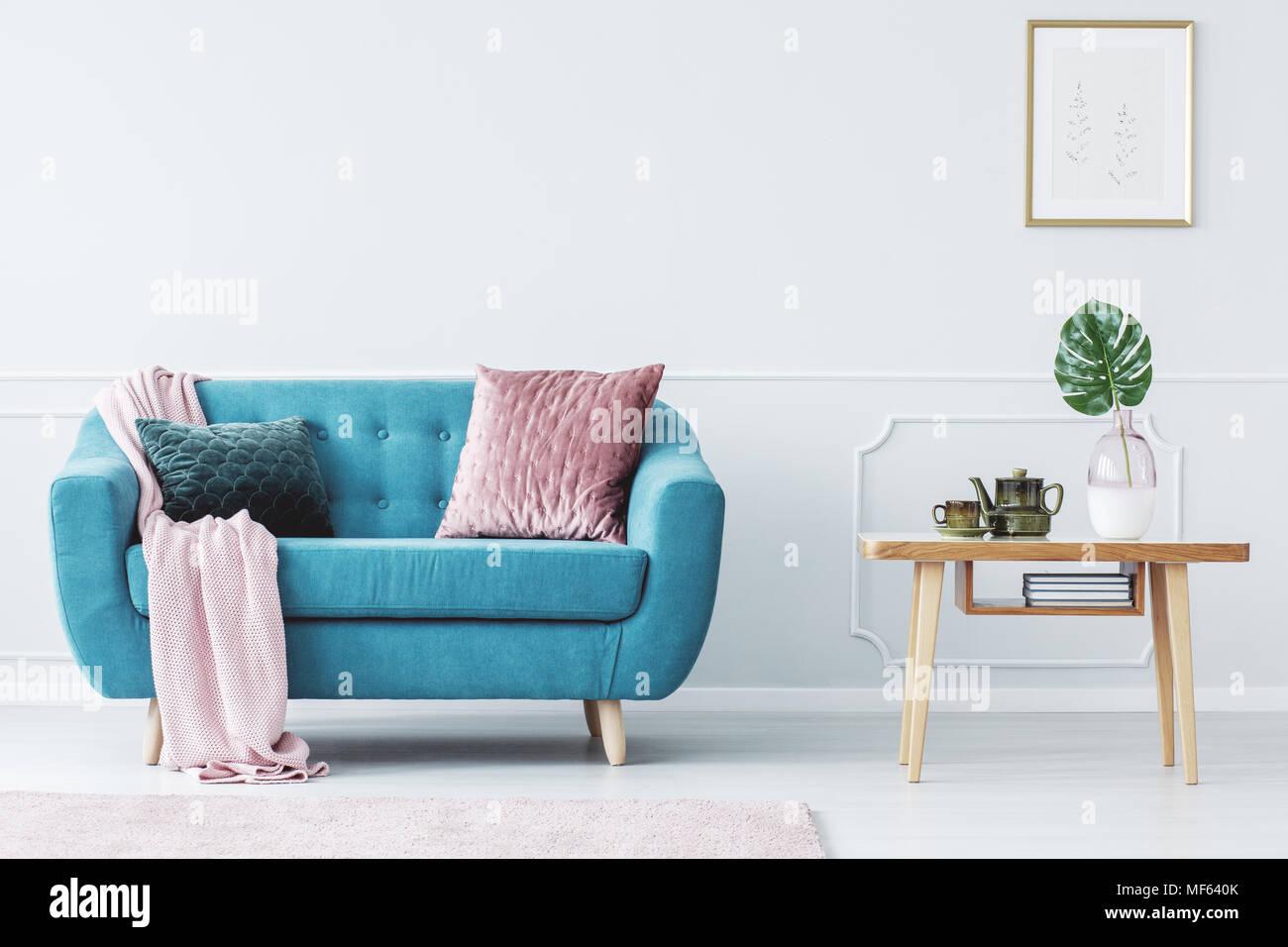 Rosa Kissen auf Türkis Couch neben Holztisch in Pastelltönen ...