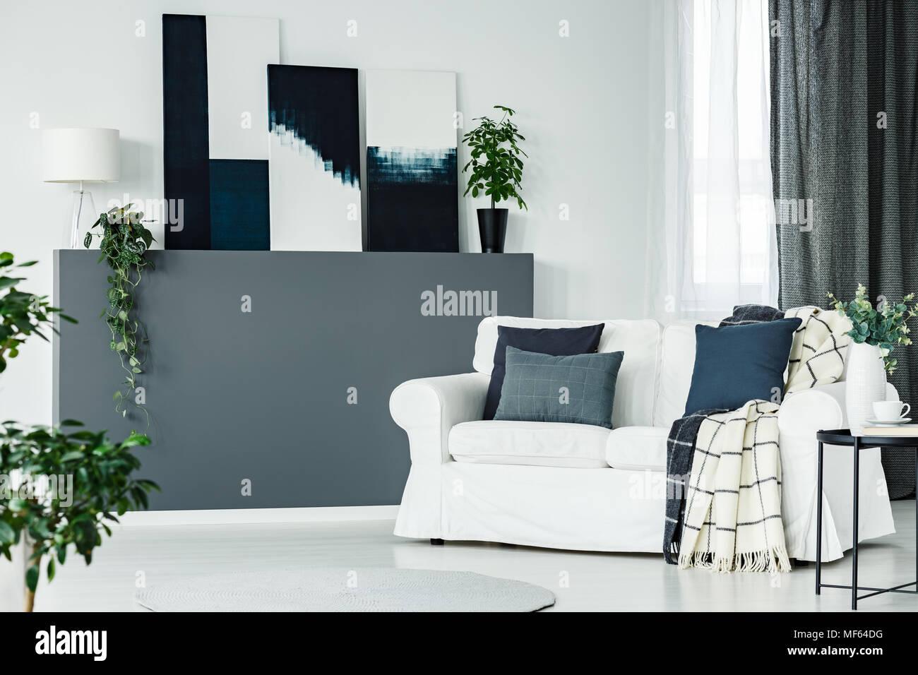 Moderne Kunst Gemälde Auf Einem Wandregal Mit Lampe Und Frische Pflanzen In  Helles Wohnzimmer Mit Fenster Und Sofa Mit Kissen Gelegt