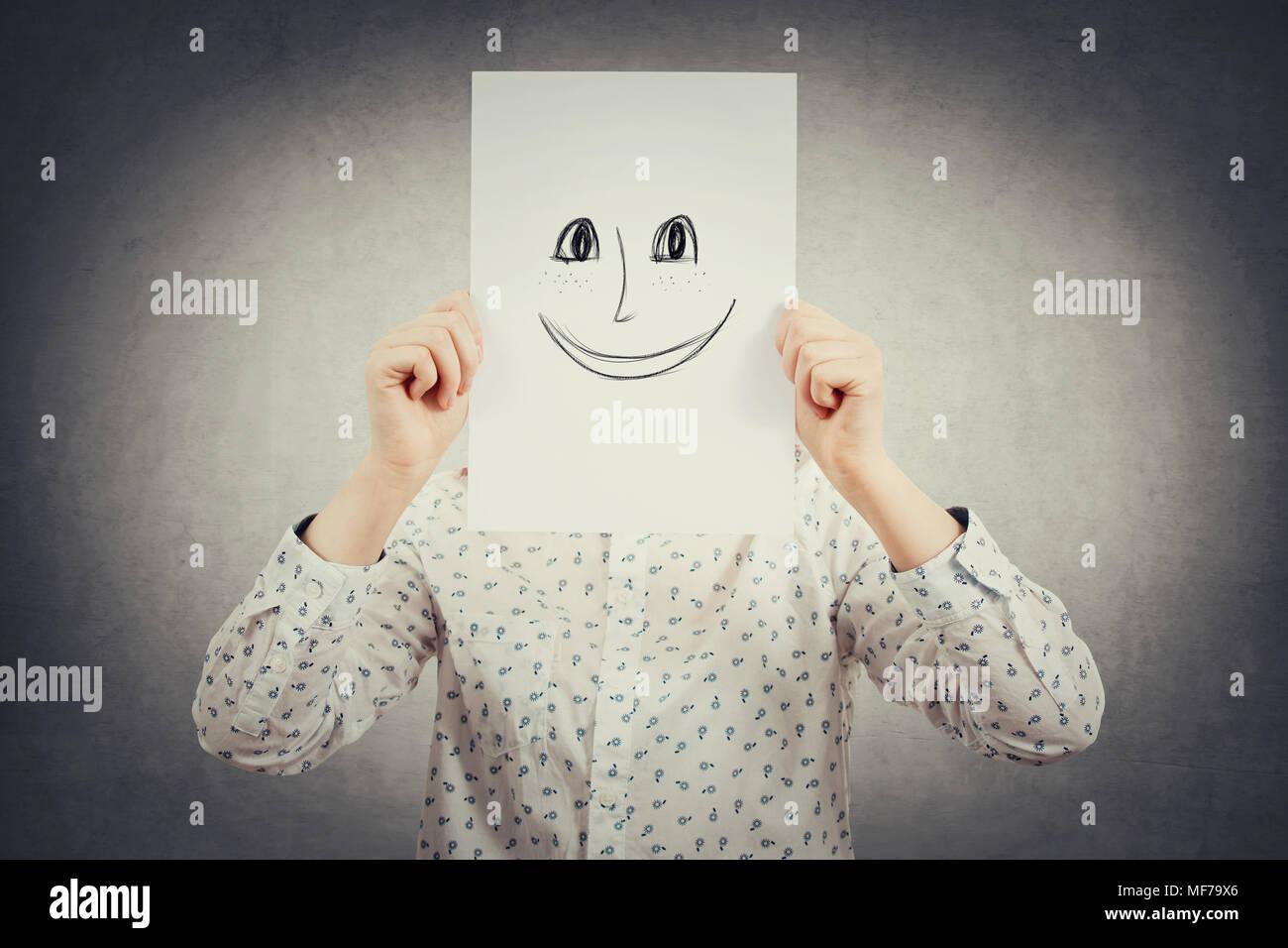 Junge Geschäftsfrau, die ihr Gesicht mit einem Blatt mit glücklichen, lächelnden Emoticon skizzieren, wie eine Maske ihre wahre Emotion aus der Gesellschaft zu verstecken. Crea Stockbild
