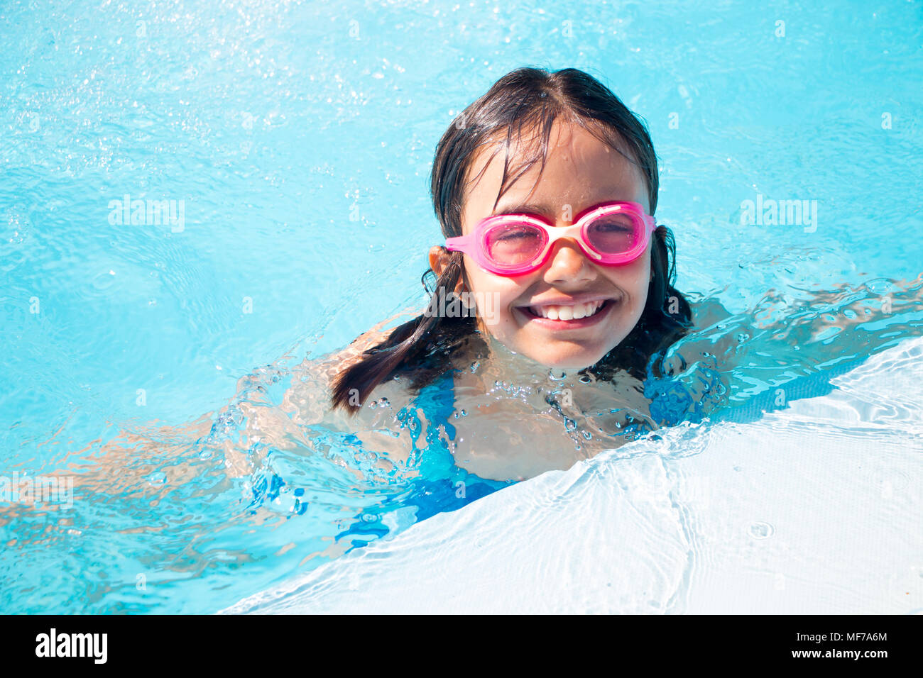 bfc69e5bcf680 Glückliche kleine Mädchen mit Brille schwimmen im Pool im Freien ...