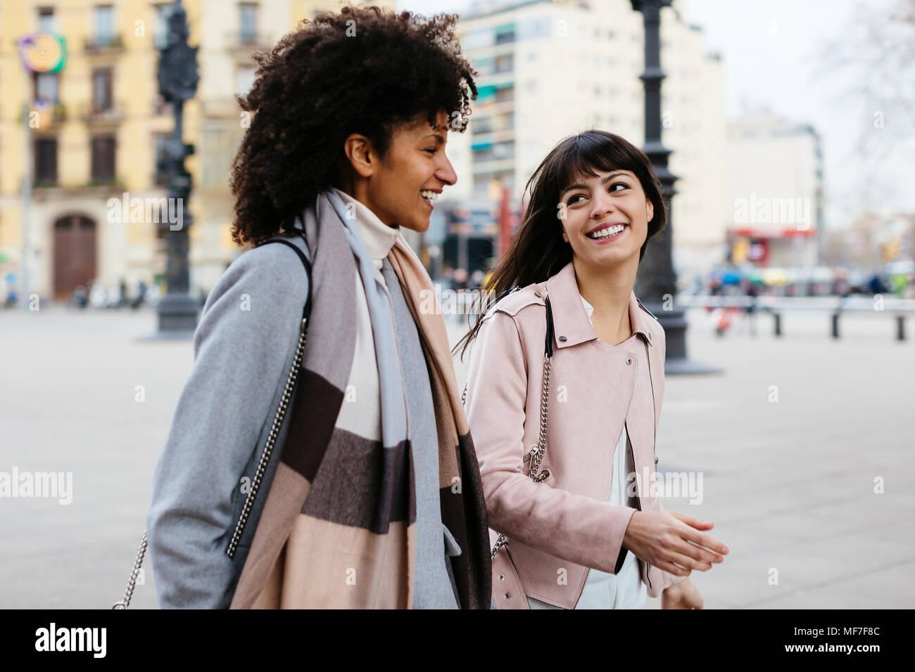 Spanien, Barcelona, zwei glückliche Frauen gehen in der Stadt Stockbild
