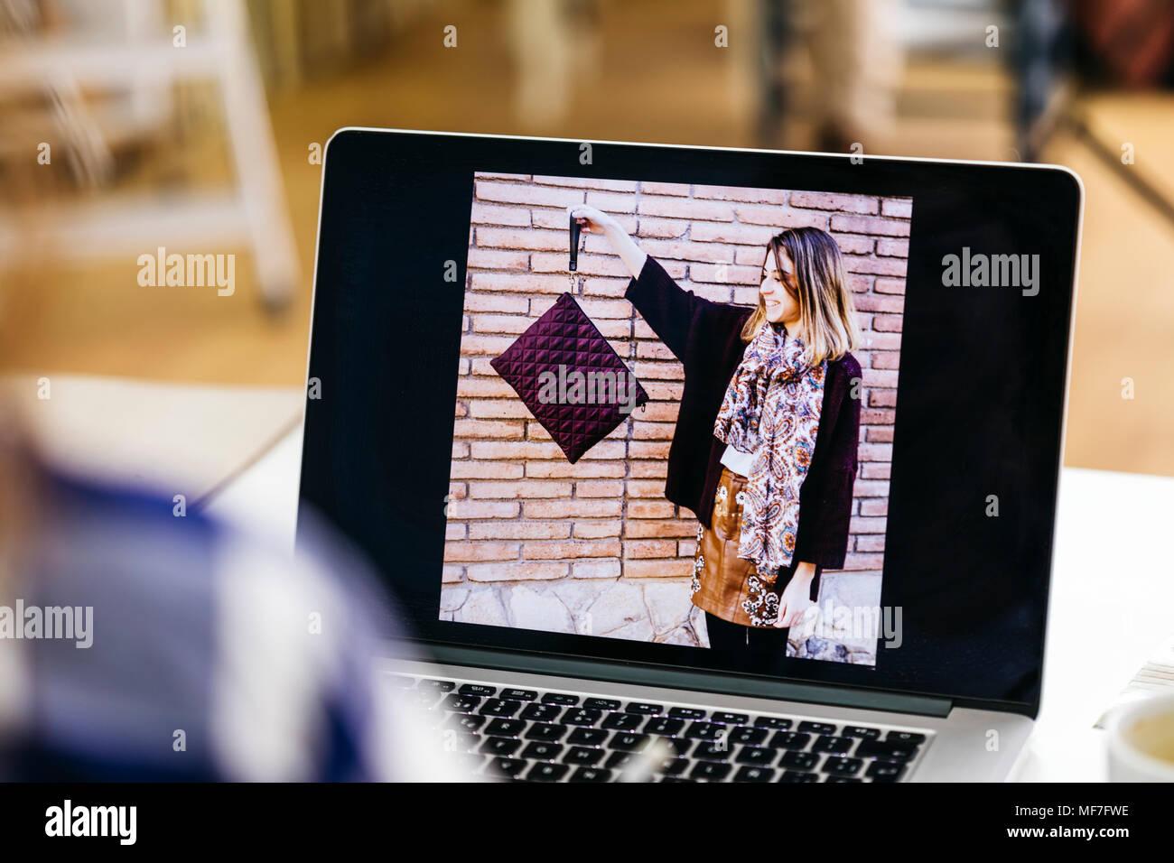 Foto von Frau mit Tasche auf dem Laptop Bildschirm Stockbild