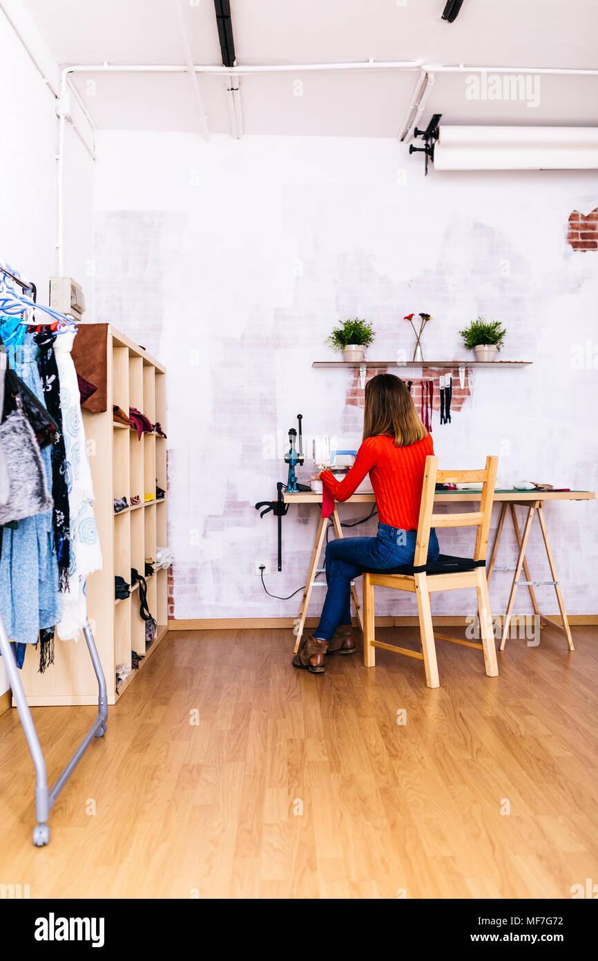 Fashion Designer mit Nähmaschine studio Stockbild