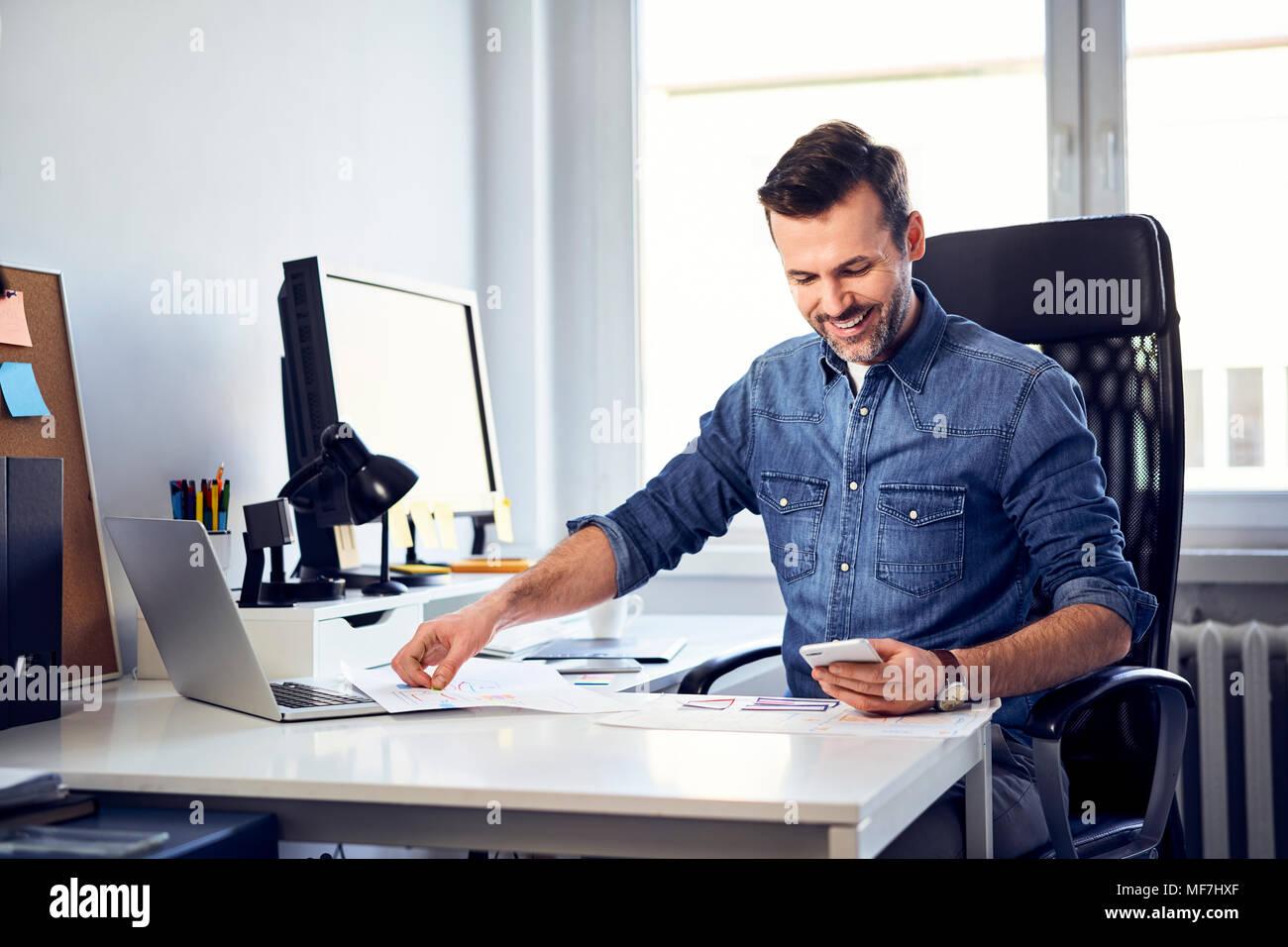 Lachelnder Mann Mit Smartphone Und Entwurf Am Schreibtisch Im Buro