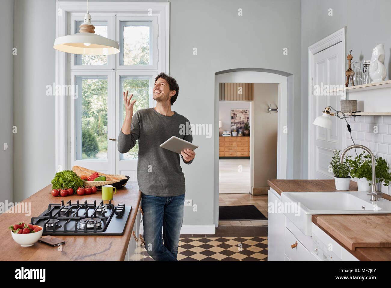 Glückliche Menschen mit Tablet in der Küche an der Decke lampe ...