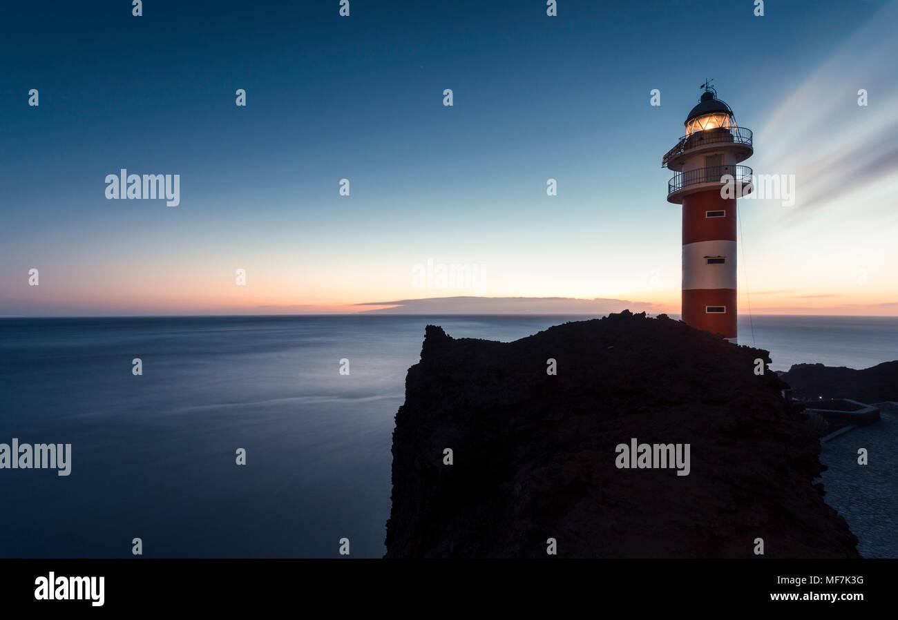 Spanien, Kanarische Inseln, Teneriffa, Punta de Teno, Leuchtturm an der Küste in der Dämmerung Stockbild