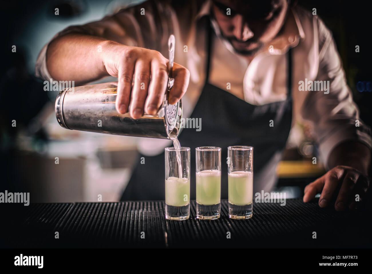 Barkeeper gießen frischen Cocktail in kurzen Glas für Service Gästebuch Stockbild