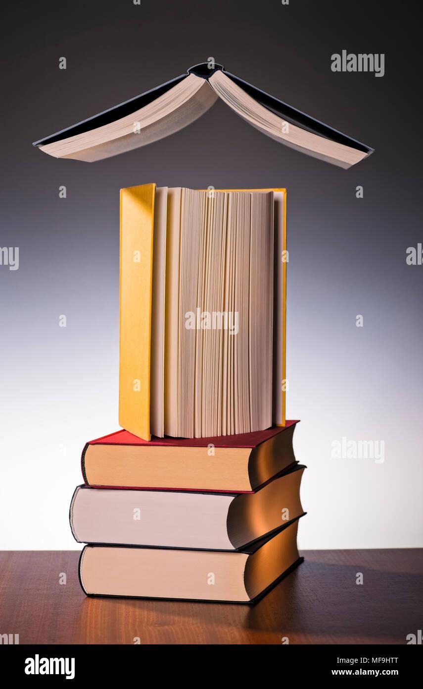 Drei gestapelte Bücher mit einem Buch und einem Schweben über Sie alle. Stockbild