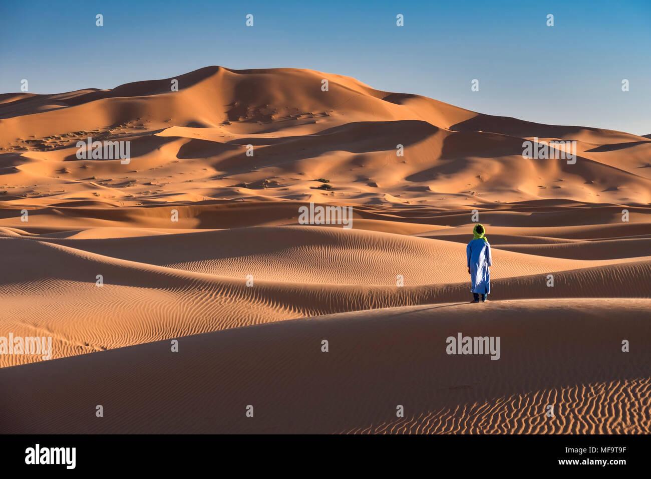 Ein Berber Mann steht am Rande der Sahara, Erg Chebbi, in der Nähe von Fes, Marokko MODEL RELEASED Stockbild