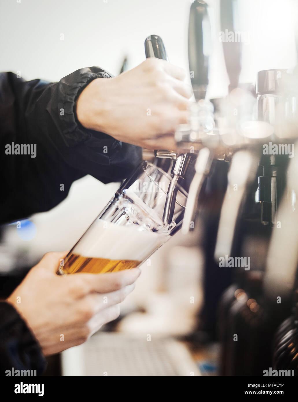 Barkeeper Mann poors Glas Bier. Stockbild