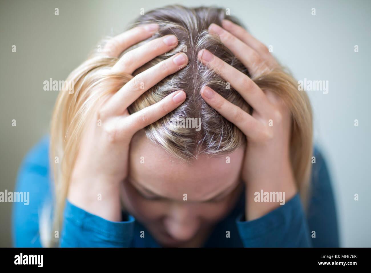 Junge Frau, die unter Depressionen leiden, mit Kopf in den Händen Stockbild