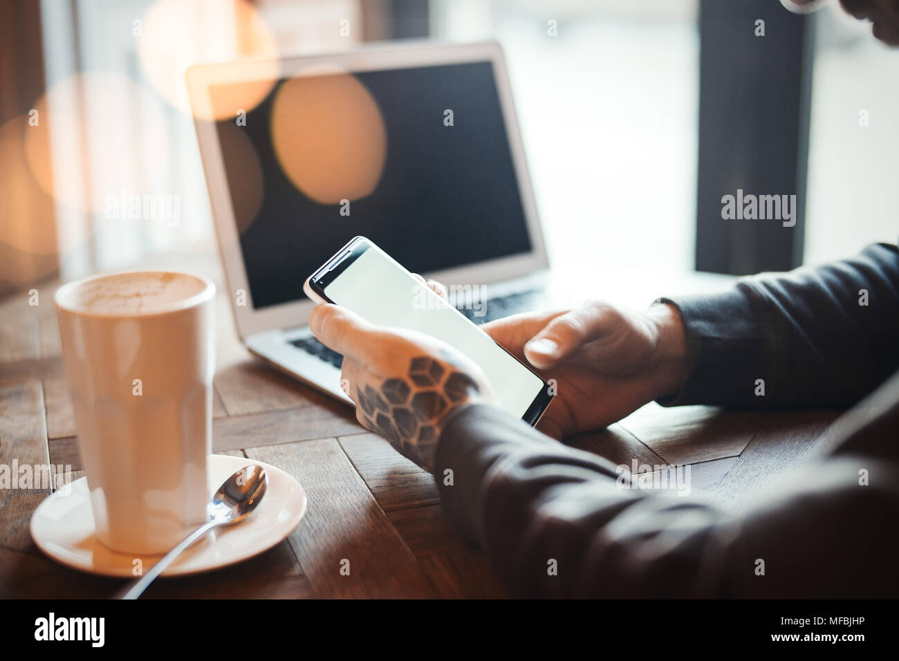 Junger Mann mit Tattoo holding Handy und Arbeiten am Laptop im Co-Arbeiten. Telefon sind auf der Vorder- und auf konzentrieren. Kaffeetasse sind auf Hintergrund Stockbild
