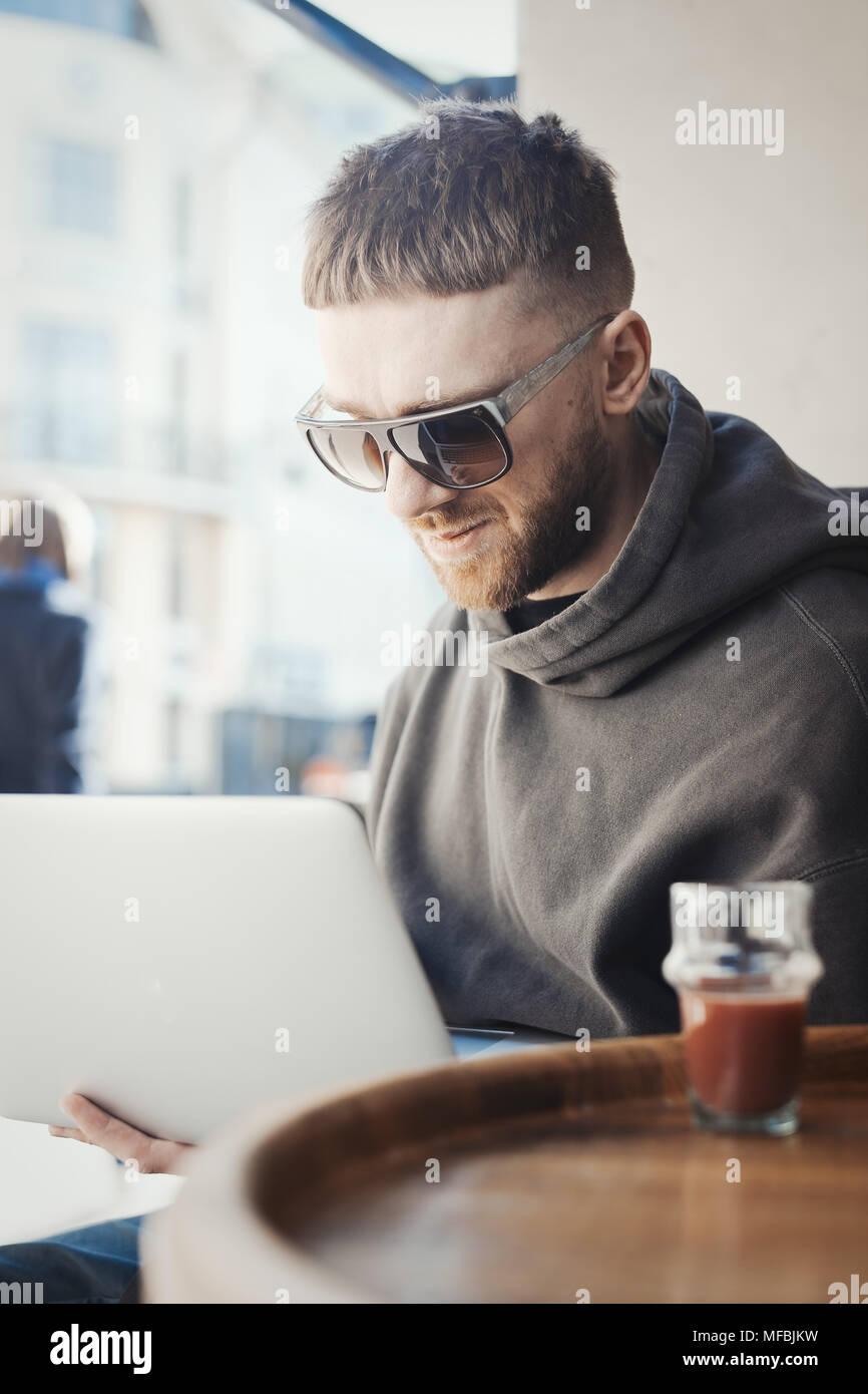 Nachdenklicher junger Mann mit Laptop auf den Knien und die Arbeit an t im Cafe. Der Mensch ist auf den Fokus und Hintergrund. Tee ist auf Vorder- und verschwommen. Stockbild