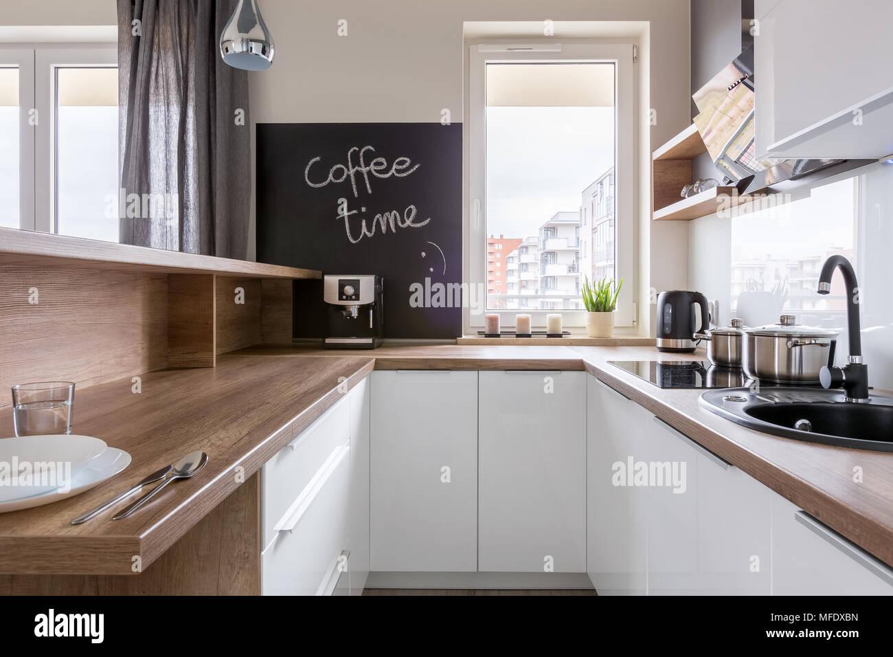 Küche mit Holz- Arbeitsplatte, weißen Schränke und auf dem Schwarzen ...
