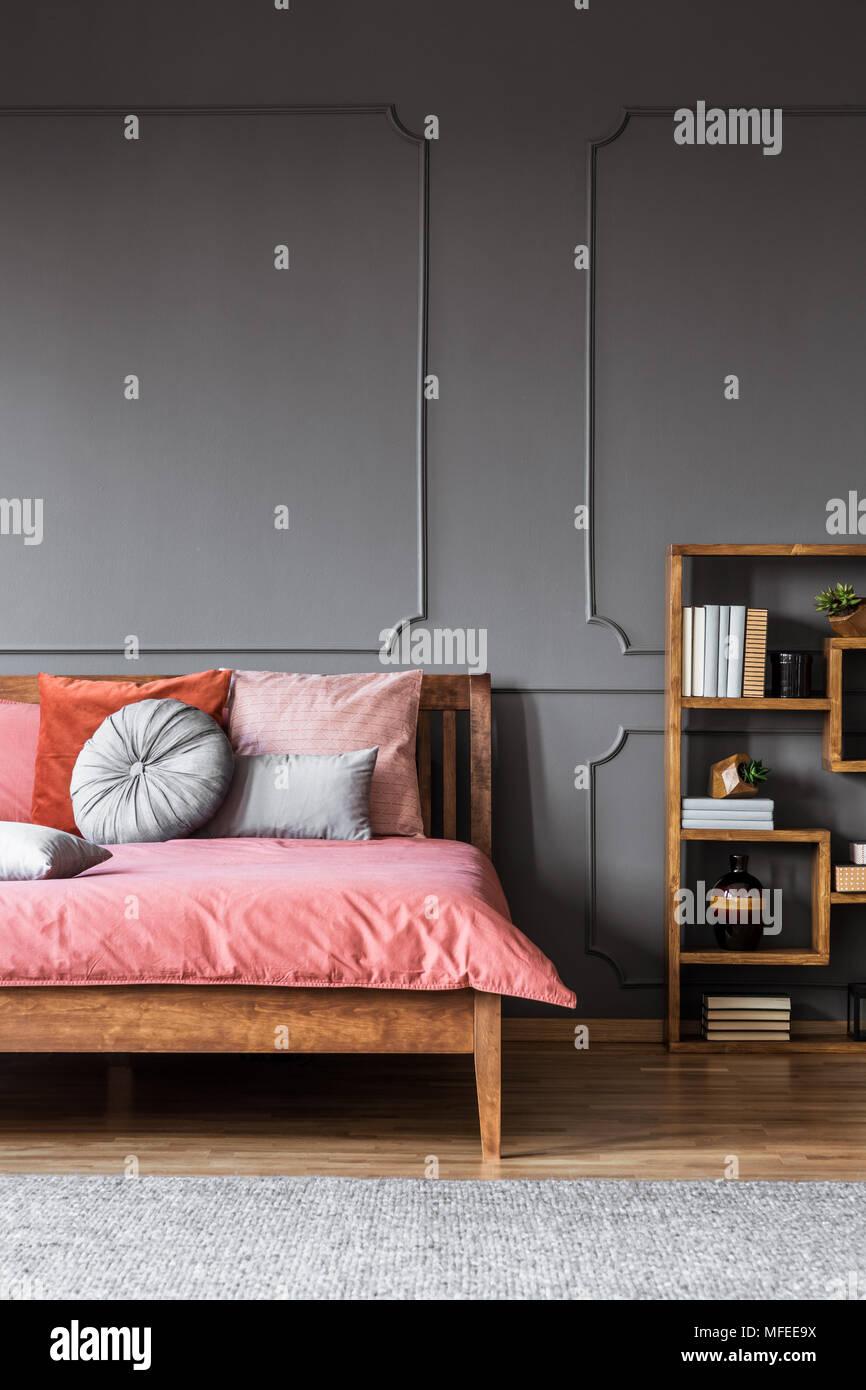 Gemütliches Bett Steht Neben Einem Regal Mit Büchern Und Ornamente In Einem  Zimmer Innen Mit Grauem