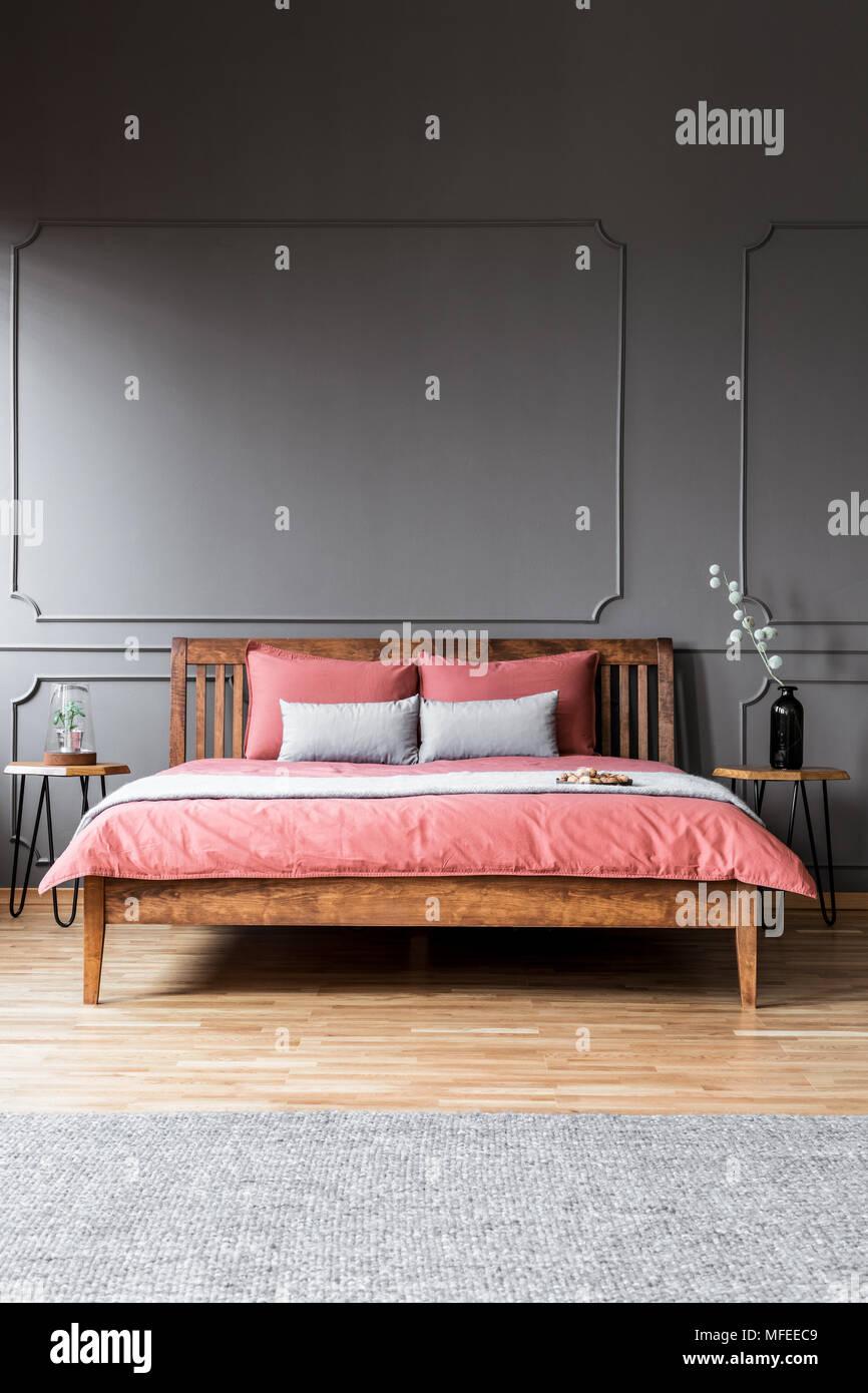Ein Grosses Bett Stand In Einem Dunklen Schlafzimmer Innenraum Zwischen Nachttische Und Vor Einem Grauen Teppich Stockfotografie Alamy