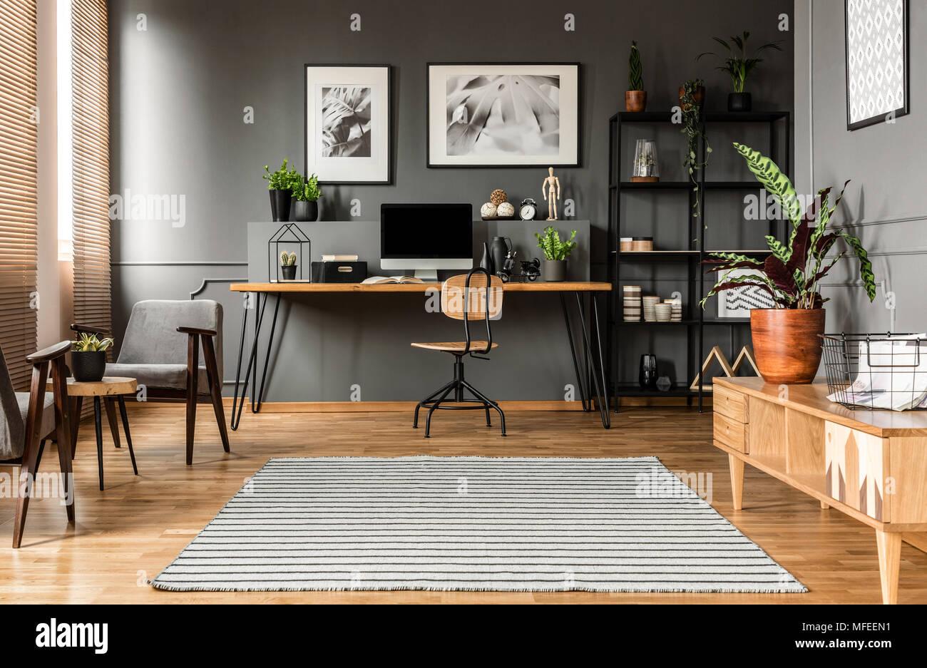 Holz Stuhl am Tisch mit Computer Monitor in der Freiberufler Inneneinrichtung mit Poster Stockbild