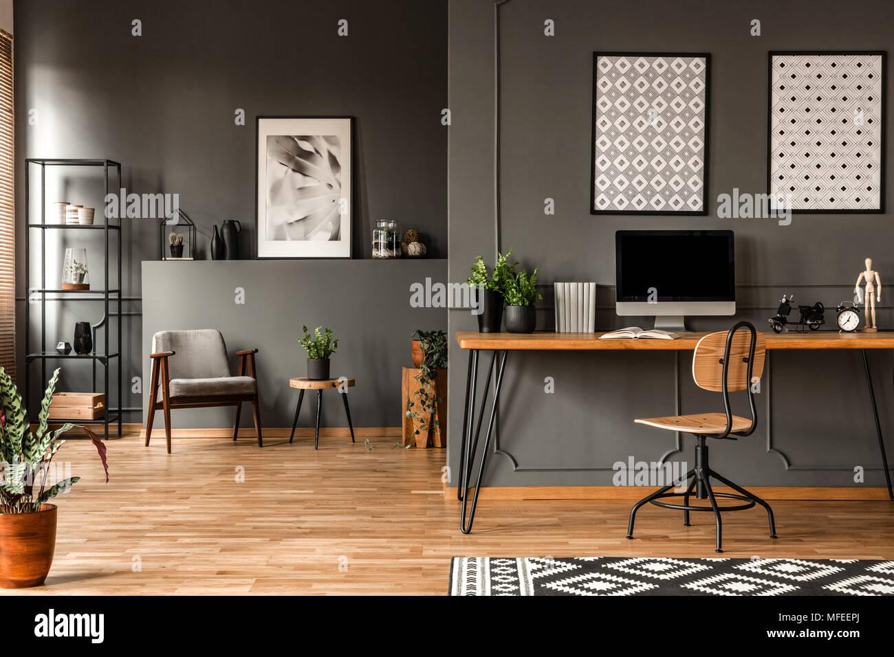 Gemusterte Poster über dem Schreibtisch mit computer monitor Grau home office Einrichtung mit Pflanzen Stockbild