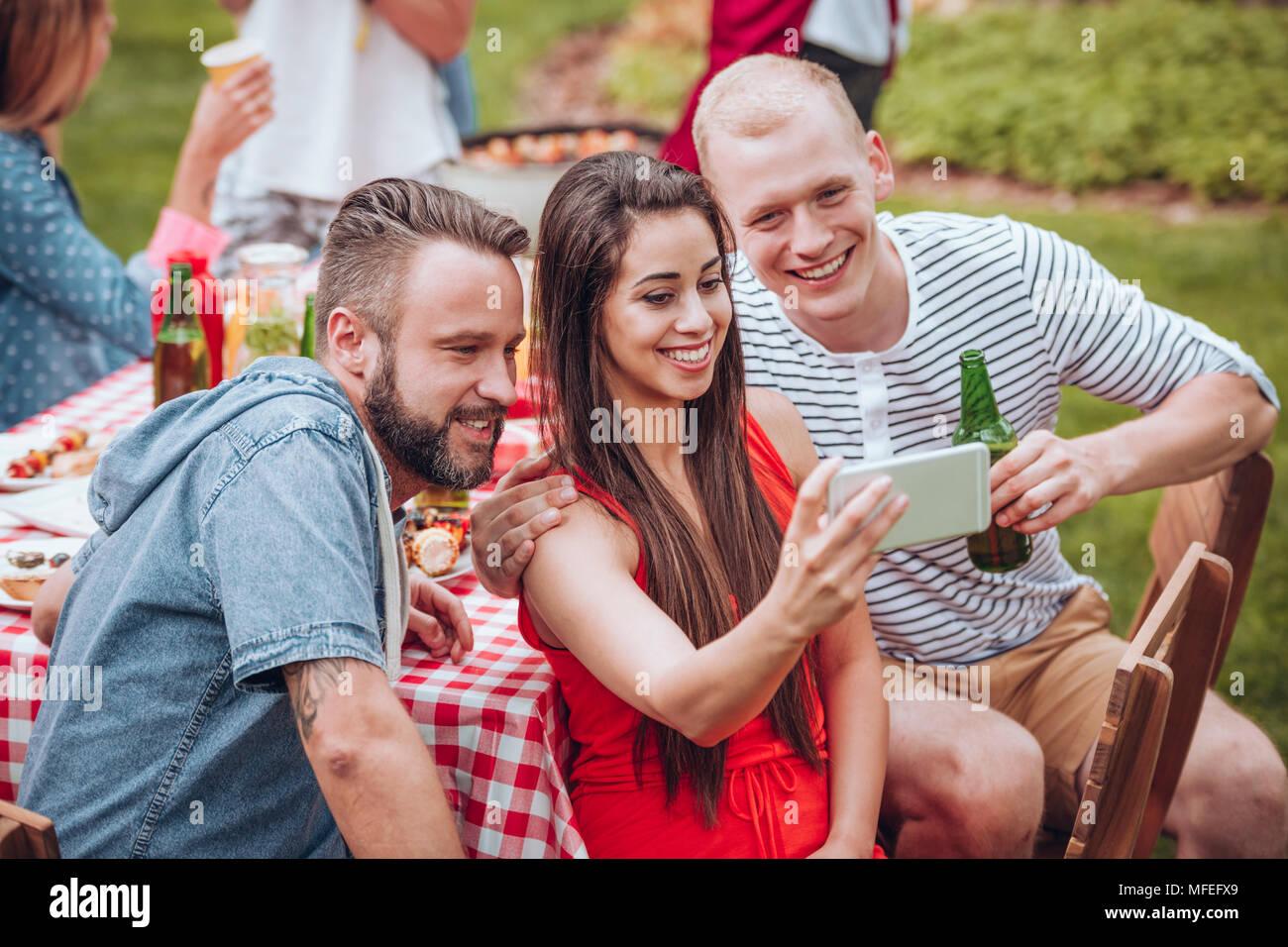 Gruppe junger Freunde sitzen um einen Tisch und nehmen eine selfie im Frühling Wochenende Outdoor Picknick im Garten Stockfoto