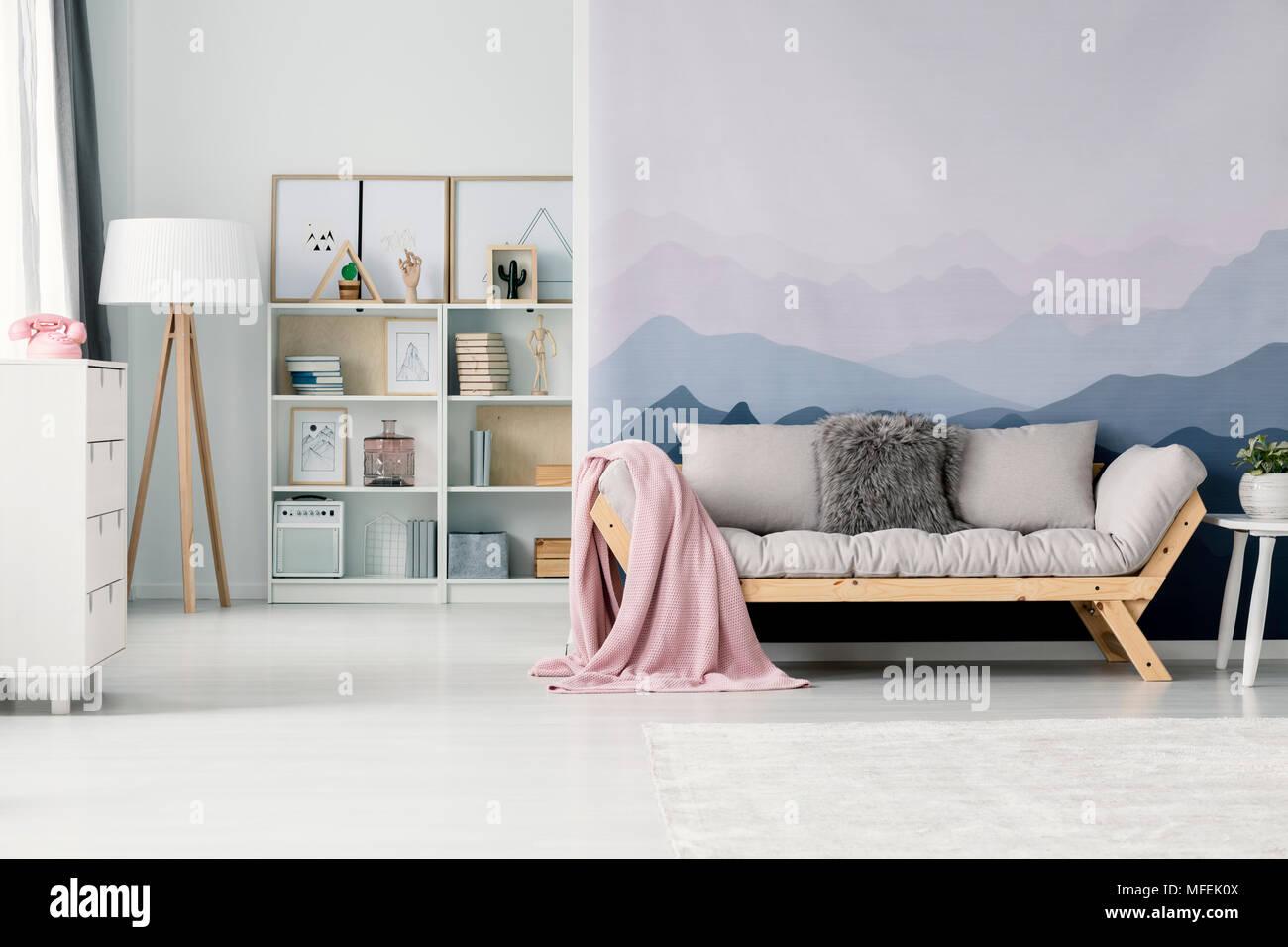 Gemütliches Wohnzimmer Mit Pastell Rosa Decke Auf Einem Beigen Sofa Gegen  Eine Wand Mit Berg Wallpaper Stehend