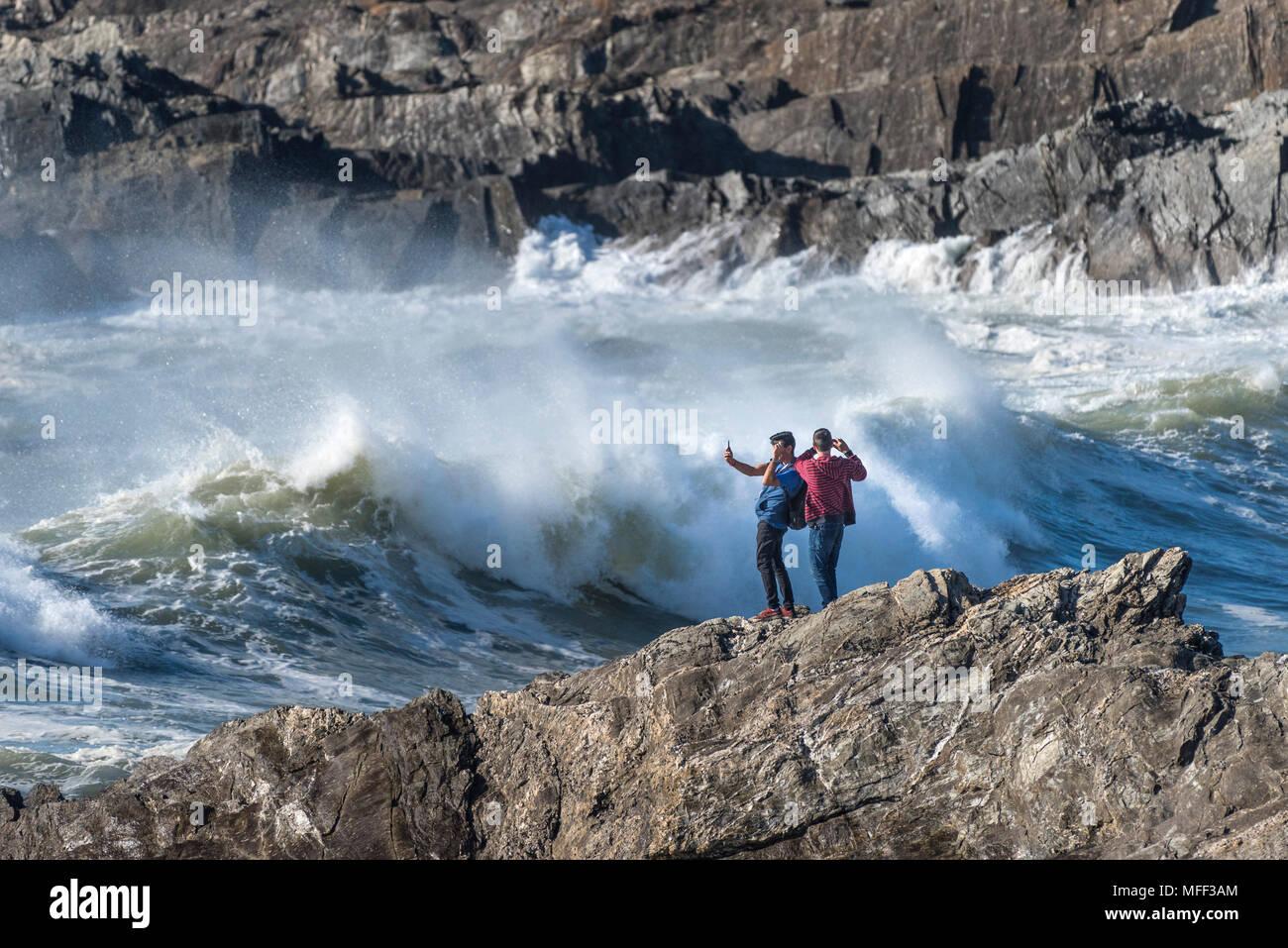 Touristen stehen auf Felsen die Fotografie als große mächtige Wellen brechen am Ufer an wenig Fistral in Newquay Cornwall. Stockbild
