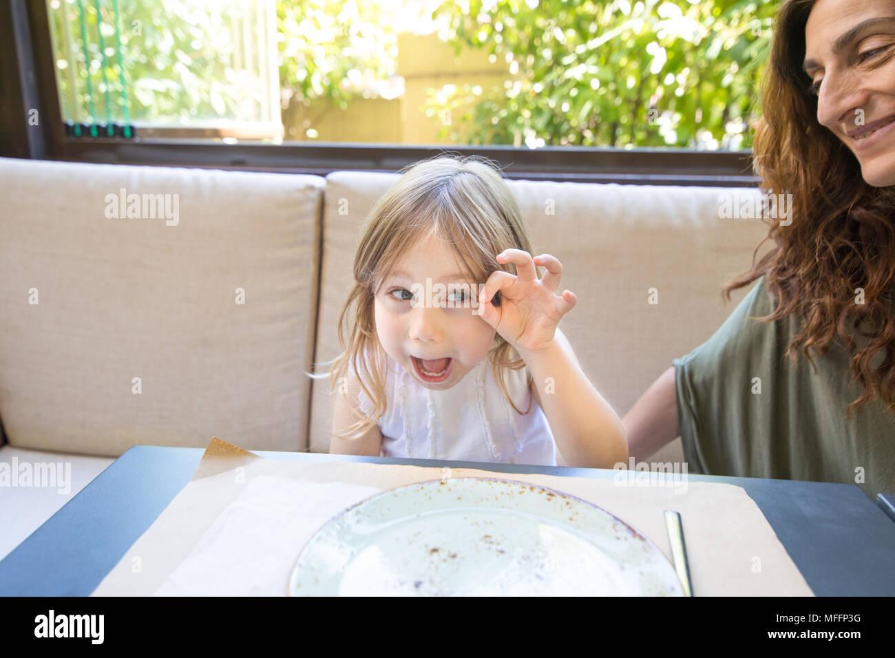 Lustige Ausdruck und Geste. Vier Jahre alter Blonde glückliches Mädchen necken und Grimassen neben Frau Mutter lächelnd sitzen im Restaurant Stockbild