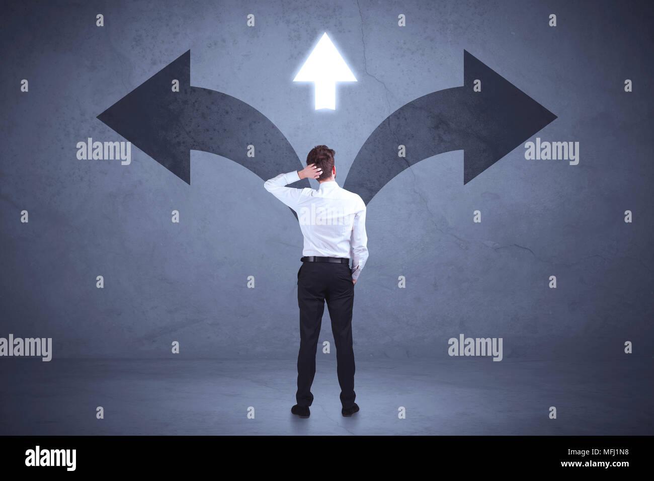 Unternehmer die Entscheidung während Pfeile an der Wand Konzept Hintergrund Stockbild