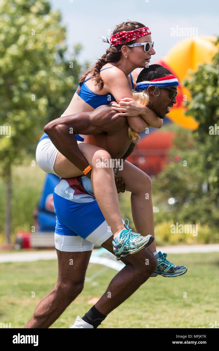 Ein athletischer Mann trägt eine Frau huckepack, wie Sie Rennen in einem der Spiele der Kid's in Atlanta Feld Tag gespielt, am 16. Juli 2016 in Atlanta, GA. Stockbild